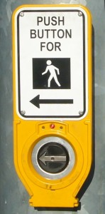 Yellow pushbutton with silver raised arrow on black background
