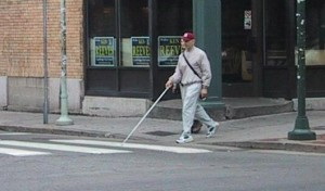 Person with white cane stepping out into a crosswalk