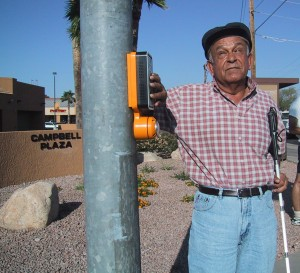 Older man with white cane stands with his hand on arrow above pushbutton